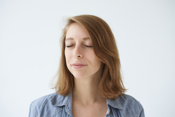 Headshot of positive young female posing at white studio wall with closed eyes while meditating, relaxing her mind, having calm and peaceful expression on her freckled face. Meditation and relaxation