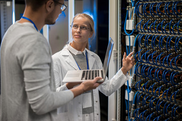 Portrait of young man and woman standing by server cabinets and discussing data while working with supercomputer in science center