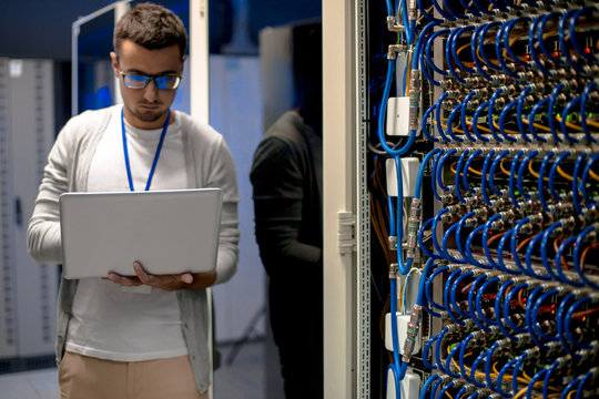 Portrait of young man with laptop standing by server cabinet while working with supercomputer in blue light