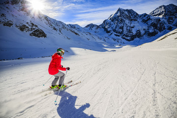 Teenager skiing in Italian Alps. In background blue sky and shiny sun and Ortler in South Tirol, Italy.  Adventure winter extreme sport.