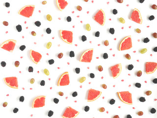Concept of healthy food. Berries and fruit pattern. Blackberries, grains of pomegranate, black and green grapes on a white background.Composition of berries and fruits, top view.