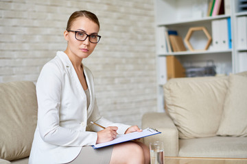 Attractive young psychologist in eyeglasses posing for photography while taking notes on clipboard, interior of cozy office on background