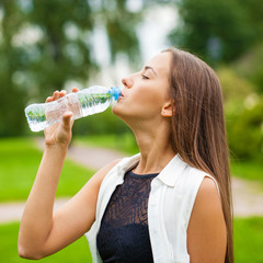 Portrait of young beautiful dark haired woman drinking water