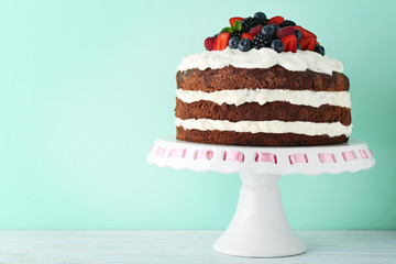 Delicious chocolate biscuit cake with berries on cake stand