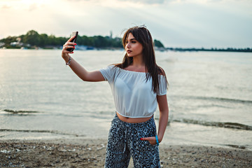 Beautiful young brunette taking selfie at the beach