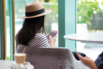 Woman using mobile phone sit on sofa at hotel lobby