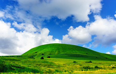 Photo sur Aluminium Colline Green Grass Hill and Blue Sky