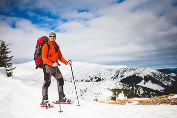 Male tourist in snow snowshoes.