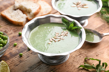 Delicious puree from green peas in bowl on wooden table