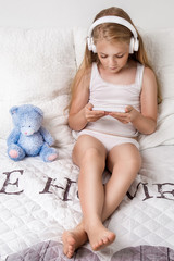 Gracious young beautiful blonde girl, little princess with long hair and blue eyes, the child lies in bed, listening to music, playing the game on a laptop computer and smiles joyfully