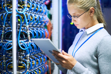 Portrait of young woman wearing glasses using digital tablet standing against server cabinets in data center