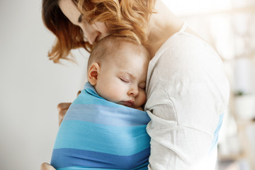 Precious little newborn boy having deep sleep at day on mother chest in blue baby sling. Mom kissing baby head and feeling relaxed and delight. Family concept.