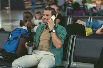Joyful man is sitting on bench in departure area