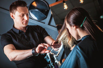 Hairdresser cutting hair, does a hairstyle of girl client. Hairstylist serving client at barber shop.