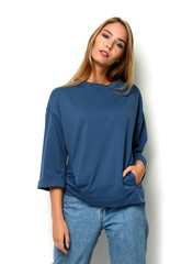 Young happy beautiful woman posing in new fashion blue jeans and pullover