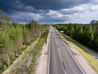 View from above at country asphalt highway among northern wood. Rain clouds in the sky. Summer season, Karelia, Russia