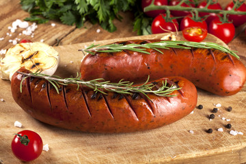 Grilled sausages on wooden background
