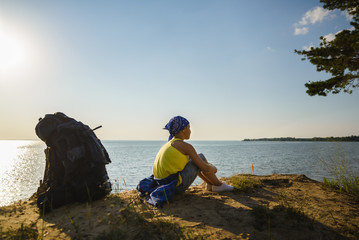 Boy sitting on sand cliff looking to sea. Travel and tourism concept