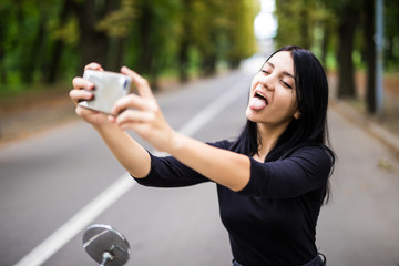 Outdoor portrait of pretty young woman sitting on scooter taking selfie on her smart phone.