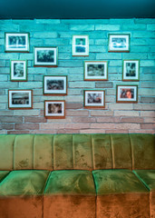 Decorated brick wall and sofa in caffee bar interior