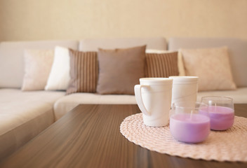 Coffee table with cups and candles in modern living room