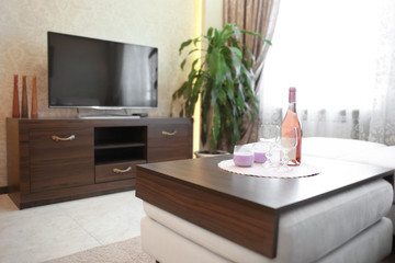 Table with glasses and bottle of champagne in modern living room
