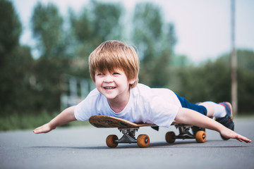Smiling little boy on skateboard outdoor.