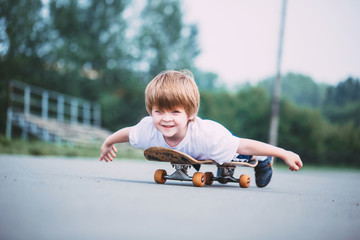 Happy little boy on skateboard outdoor.