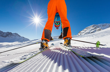 Skier posing on piste in high mountains