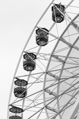 Ferris wheel hanging gondolas. Black and white photo showing rim and spokes.