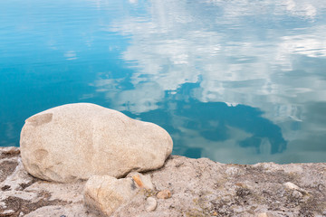 Large rock with calm blue water background close up. Cloud reflections.