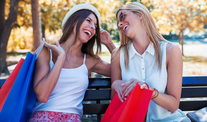 Shopping time. Beautiful women resting in the park after shopping. Consumerism, shopping, lifestyle concept