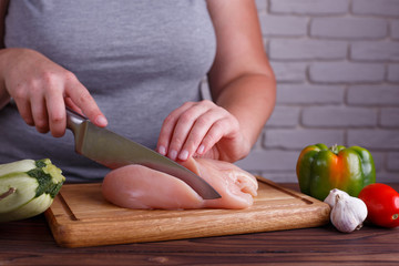 Overweight woman hands chopping up chicken breasts. Dieting, healthy low calorie food, weight losing concept