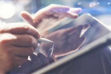 Closeup view of businessman holding tablet on hand and using electronic pen while working at office.Pointing tablet screen.Blurred background.Horizontal.