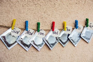 condoms on colorful clothespins. seven days of the week - sexweek, space for text. selective focus image