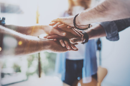 Teamwork business concept.Close up view of group of three coworkers join hand together during their meeting. Horizontal.Blurred background.