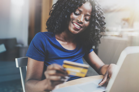 Happy young african american woman shopping online through laptop using credit card at home. Horizontal,blurred background.Cropped.