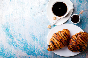 Breakfast Continental  with Fresh  Croissants on a blue Background Coffee  and milk Delicious Baking with  with Chocolate Topping  Top View Copy space for Text