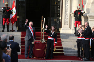 Peru's President Pedro Pablo Kuczynski and new Economy Minister Claudia Cooper wave during her swearing-in ceremony at the government palace in Lima