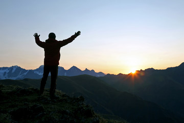 man with raised hands standing on the mountain face to sunrise.