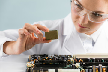 Woman engineer looking at a circuit board.
