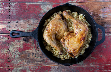 roasted chicken thighs over rice in cast iron pan top view