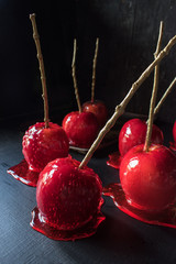 group of red candy apple dripping with sugar on dark background