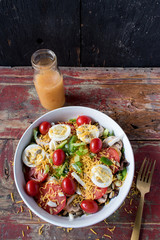 garden salad with tomatoes, cheese, and eggs with fork and dressing