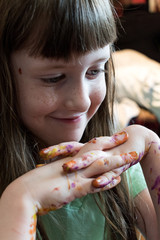 smiling young artist with painted fingers
