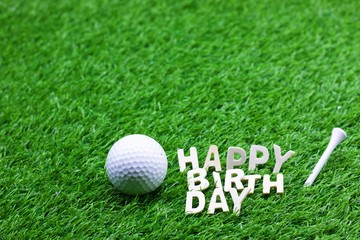 Happy birthday to golfer word on green grass with golf ball