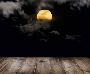 Halloween background. Wooden table over full moon with clouds at night.