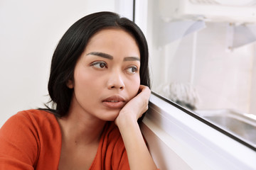 Portrait of asian woman daydreaming and looking through a window