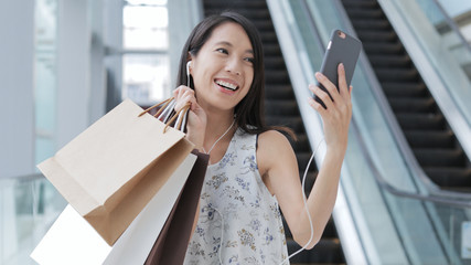 Woman making video call with cellphone and holding shopping bags