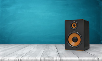3d rendering of a one black speaker box with orange trim standing on a wooden table in front of a blue background.